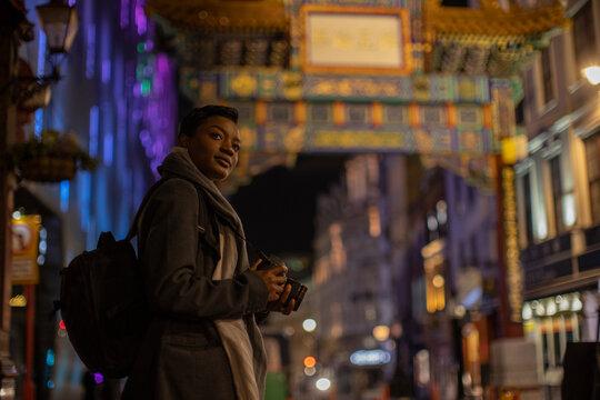 Young woman with digital camera at Chinatown Gate at night, London, UK