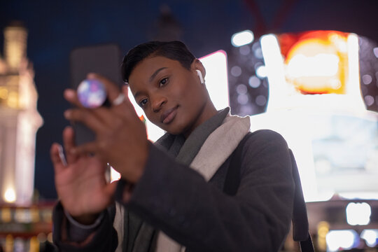 Young woman taking selfie below neon billboard in city at night