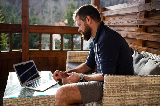 man working on laptop in wooden cottage