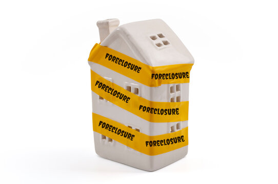 """Home bankruptcy, mortgage loss mitigation and foreclosed property concept with ceramic house wrapped in yellow tape with the text """"foreclosure"""" isolated on white background with clipping path cutout"""