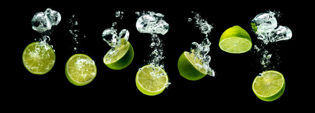 Bunch of lime fruits halves sinking with bubbles into water isolated against black background. Citrus theme, panorama