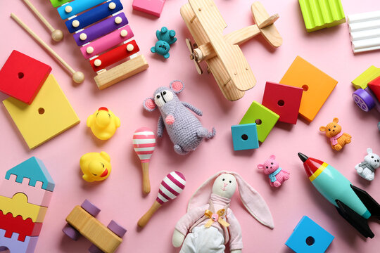 Different toys on pink background, flat lay