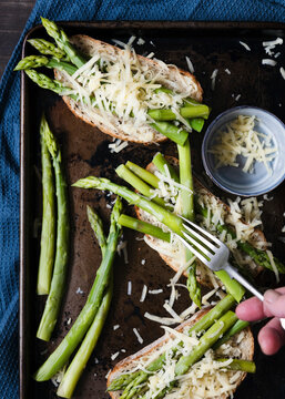 Asparagus spears and grated cheese on sourdough bread.