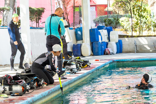group of 4 divers having a good time preparing their equipment to enter the water