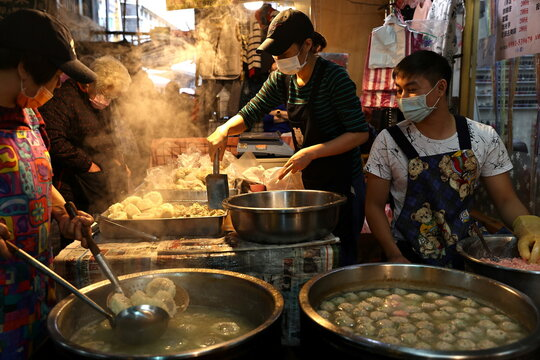 People wear protective masks to prevent the spread of the coronavirus disease (COVID-19) while selling meatballs in a market in Taipei