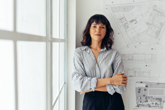 Confident female architect standing in office
