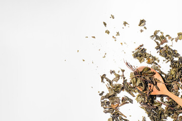 Dry fruit tea leaves in a wooden spoon. Scattered tea leaves on white background, top view copy space Wall mural