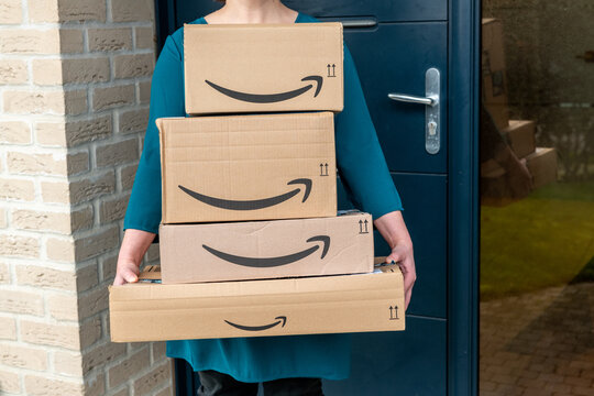 Lille, France - December 18, 2020 : woman carrying amazon packages in front of her house entrance