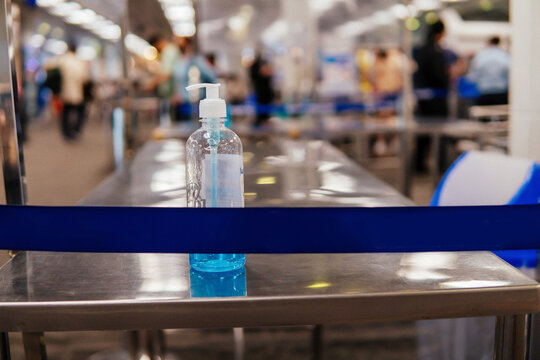 Hand sanitizer on table in the airport terminal to prevent Corona Virus pandemic from spreading. Public Transportation during Covid-19 concept.