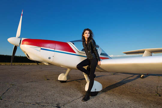 Beautiful sexy girl in a leather flight suit on a sunny day with a blue sky against the background of a small two-seater plane