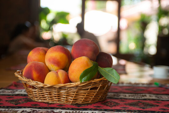 Fresh peaches fruits with leaves in basket on rustic background