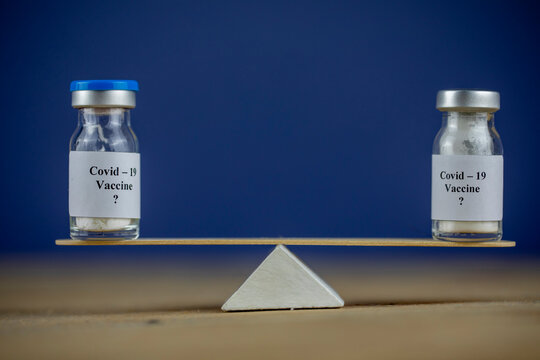 Concept of the balance of two vaccine on wooden scales,