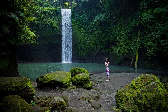 Outdoor yoga practice. Young woman standing near waterfall. Hands in namaste mudra, closed eyes. Preparing for Sun salutation Surya Namaskar. Yoga retreat. Tibumana waterfall, Bali