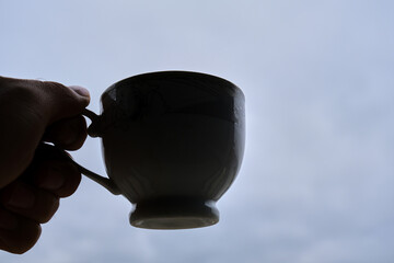 Cute coffee pot silhouette with overcast sky background. Pot hold by a hand. Fotobehang