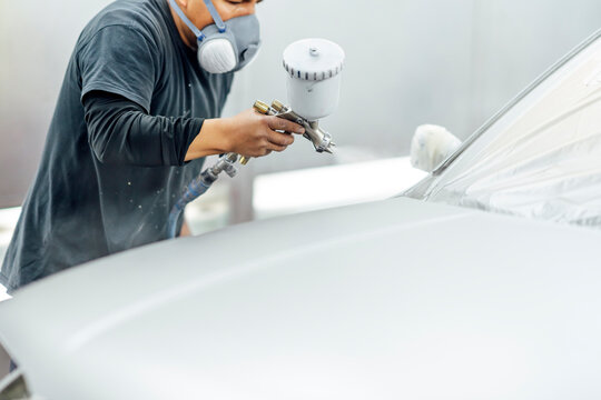 Close-up of a bodywork mechanic working in the workshop painting a car