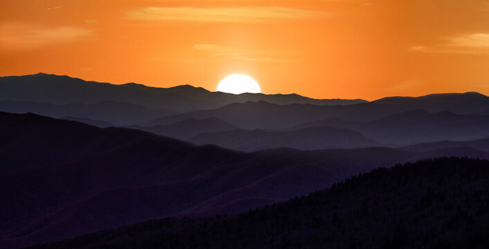 Sunset over the smoky mountains wil rolling hills