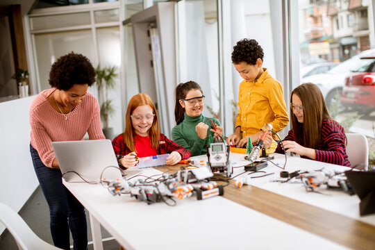 Happy kids with their African American female science teacher with laptop programming electric toys and robots at robotics classroom