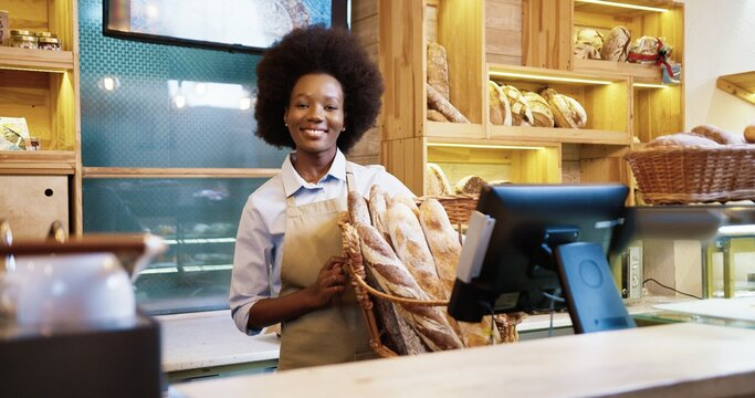 Happy beautiful African American young woman entrepreneur in apron stands in own small bakery holding fresh bread baguettes in hands and smiling to camera. Business concept