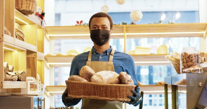 Close up of handsome happy young African American man bakery worker in face mask standing in bakehouse and holding basket with fresh baked bread. Bakery owner looking at camera and smiling