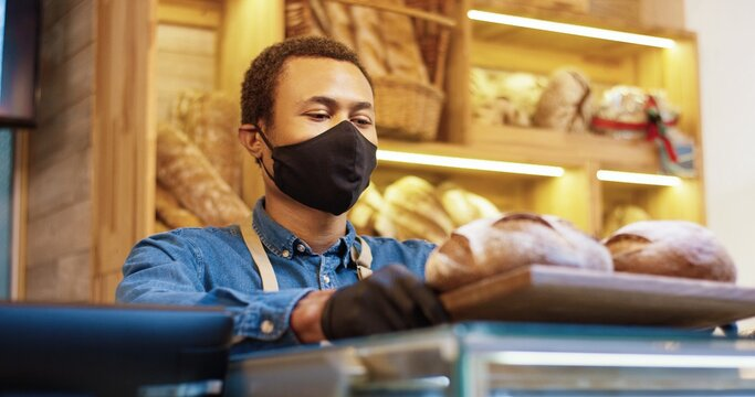 Close up of handsome young joyful African American man seller in face mask standing in bakery shop and putting tray with fresh baked bread on counter. Bakehouse owner looking at camera and smiling