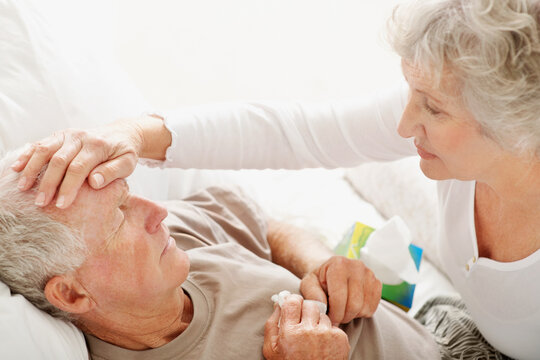 Senior woman caring for man with a fever