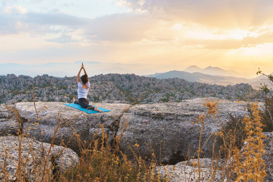 Back view of unrecognizable female performing front splits with arms raised while practicing advanced yoga on top of rock in highlands at sunset time
