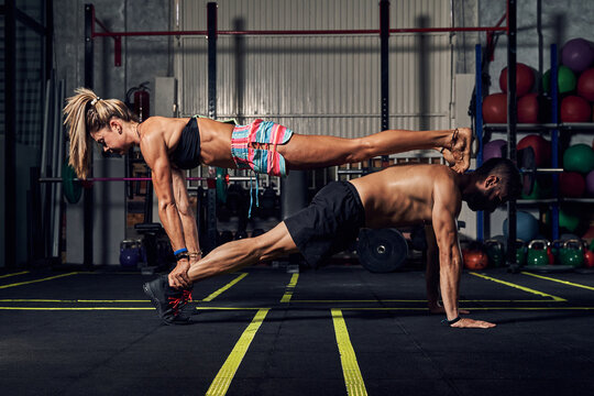 Side view of muscular young man and woman doing plank exercise together during fitness workout in gym