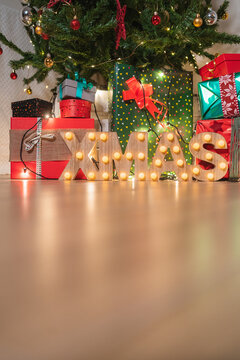 Christmas tree with wrapped presents and wooden letters of word xmas with light bulbs in cozy room