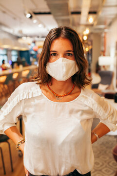 Serious young female employee in casual outfit and protective mask looking at camera while standing against blurred interior of modern coworking space