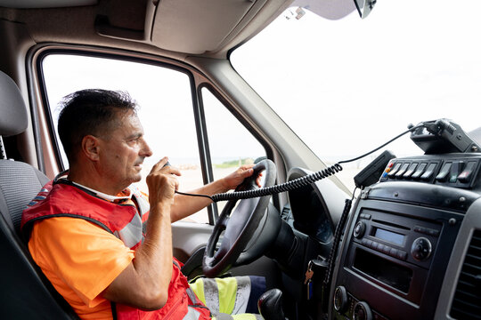 Side view of adult ambulance driver talking on walkie talkie while driving transport at work and looking forward