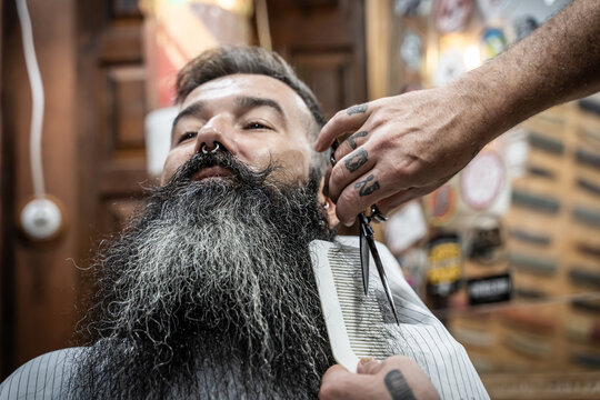 Professional tattooed barber in protective mask with comb and scissors cutting long beard of middle aged gray haired male customer while working in barbershop with vintage interior
