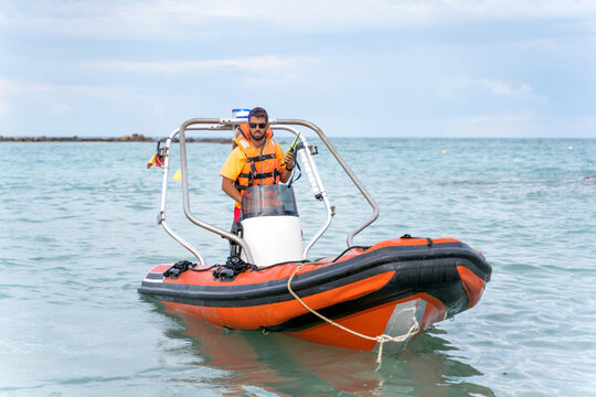 Young lifeguard in orange life vest and sunglasses standing on modern motorboat on calm rippling seawater and looking at camera