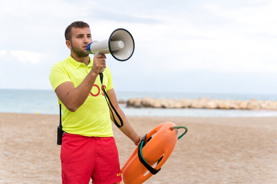 Serious male lifeguard with safety buoy talking in megaphone while standing on sandy beach