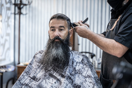 Crop anonymous barber with electric trimmer and comb cutting hair of middle aged hipster male customer with long beard and mustache in modern barbershop