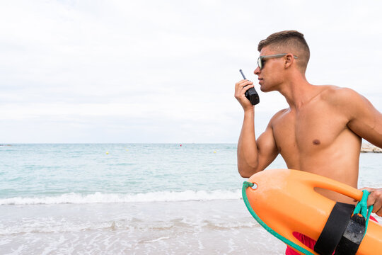 Side view of young stylish male employee with naked torso and torpedo rescue buoy talking on radio transceiver on sandy beach near ocean while looking away