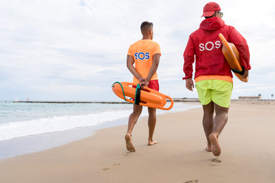 Back view of unrecognizable male friends with torpedo life savers walking on sandy shore near wavy ocean