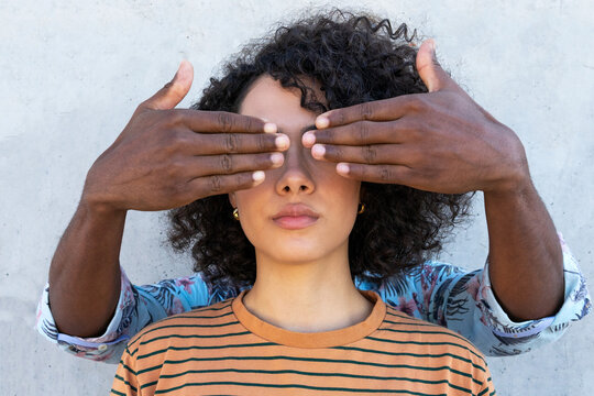 Anonymous friend covering eyes of stylish ethnic female with curly hair hairstyle near concrete wall