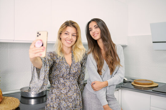 Positive young girlfriends smiling and taking selfie on mobile phone while preparing cake together in home kitchen