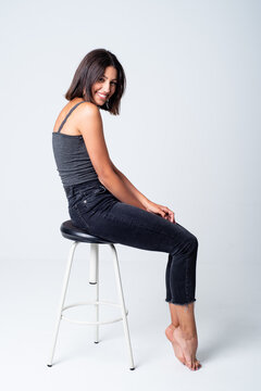 Full length young slim brunette in casual outfit sitting on stool against white background and looking at camera with happy smile