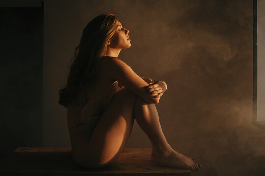 Side view of tranquil female in bodysuit sitting on wooden table and embracing knees while enjoying sunlight with closed eyes