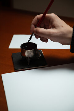 Hand dips fountain pen in inkwell