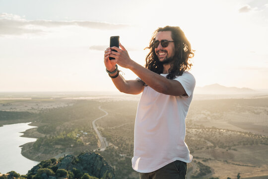 Excited young male with long curly hair standing on hill against vast spectacular valley and taking selfie on modern mobile phone