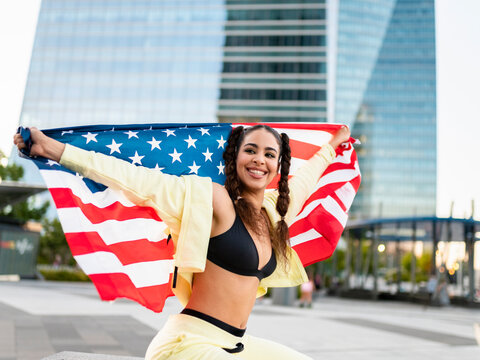 Side view of confident young ethnic lady in sports bra waving American flag and looking at camera against modern glass skyscraper