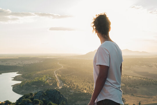 Back view faceless male with long curly hair wearing white shirt standing on sunny hilltop and admiring vast scenic valley with tranquil pond and lush greenery