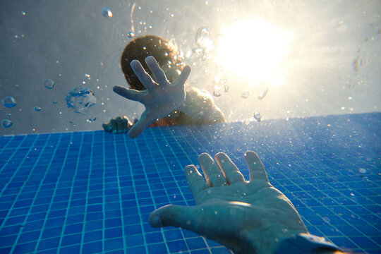 From below view of faceless boys hand reaching for sinking in swimming pool water males hand