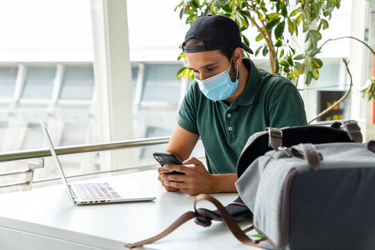 Smiling male wearing medical mask sitting at table with laptop and using cellphone