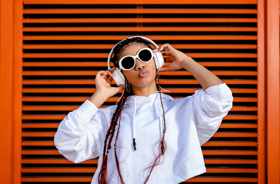 Stylish African American female in casual white wear and sunglasses listening to music with headset standing against red wall with hands on face
