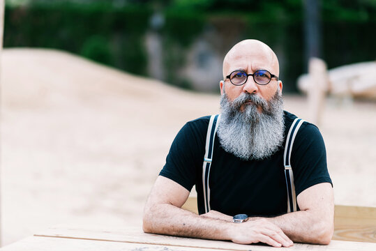 Calm senior male with bald head and long gray beard sitting at wooden table in park and confidently looking at camera