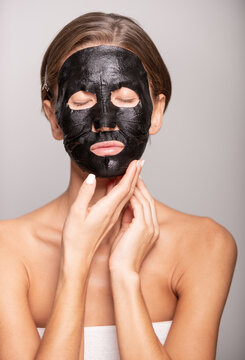 Tender female in black cosmetic mask doing daily skin treatments and standing with closed eyes on violet background in studio