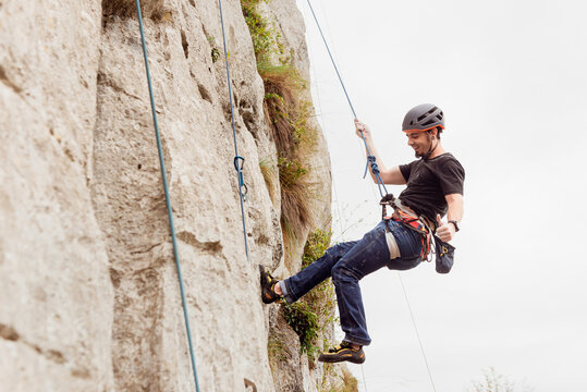 Strong male alpinist in safety equipment climbing on rocky cliff on sunny day